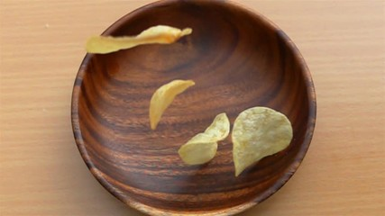 Fototapete - Potato chips fall into a wooden plate on a table in Slow Motion
