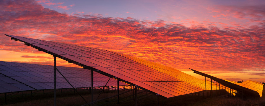 Solar power plant on the background of dramatic, fiery sky at sunset,Germany