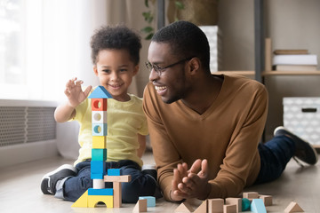 Happy little son playing with black dad using wooden blocks