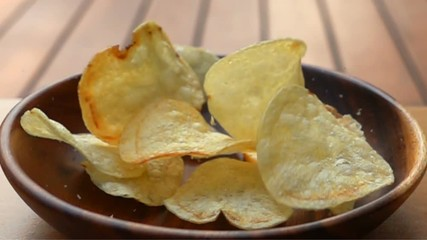 Fototapete - Closeup scene of potato chips fall into a wooden plate on the table in Slow Motion