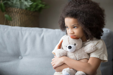 Upset lonely african kid girl holding teddy bear looking away