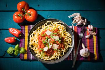Pasta al Pomodoro, Fusilli Lunghi mit Tomatensauce, Knoblauch, Basilikum, Parmesan und Pepperoni serviert auf Holztisch