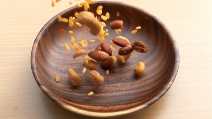 Fototapete - Mixed Nuts fall into a wooden plate on the table in Slow Motion