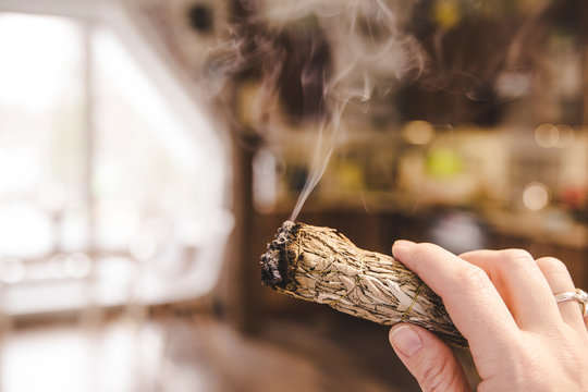 Woman hand holding herb bundle of dried sage smudge stick smoking. It is believed to cleanse negative energy and purify living spaces at home in rooms.
