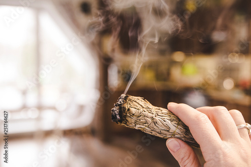 Woman hand holding herb bundle of dried sage smudge stick
