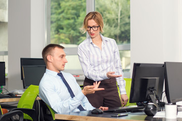 Female manager is interested in a subordinate man with information about the transaction points to a computer monitor. Conversation of employees in the office near the workplace.