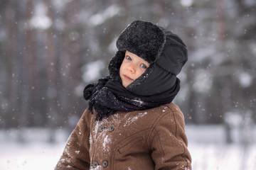 portrait of a little boy in a winter forest