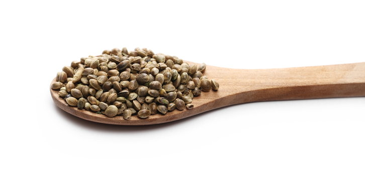Hemp seeds in wooden spoon isolated on white background