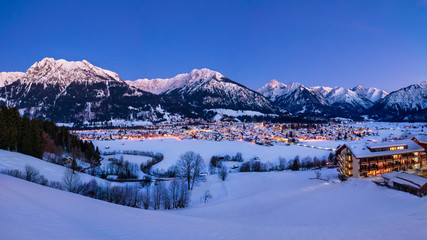 The valley Kleinwalsertal and Oberstdorf, Germany, with Alps in the winter with snow covered landscape in the evening.
