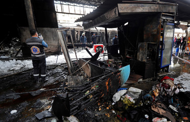 Medic takes picture with his mobile after a fire caused deaths and injuries at the main train station in Cairo