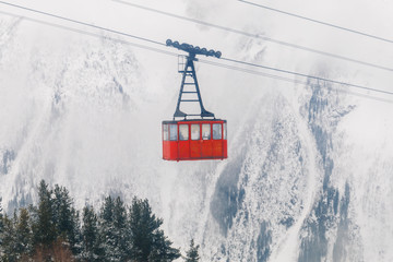 Red Ski lift in the background of the winter mountains. The red trailer of the old cable car moves to the mountain top of the ski resort. Retro gondola.
