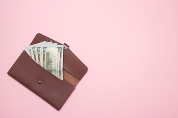 Women's wallet with money on pink background. Top view.