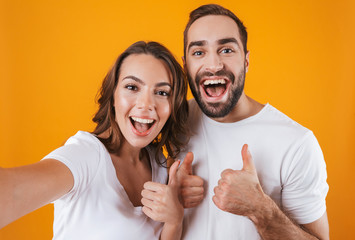 Portrait of two european people man and woman smiling while taking selfie photo, isolated over yellow background