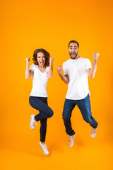 Full length photo of cheerful couple screaming in surprise while jumping, isolated over yellow background