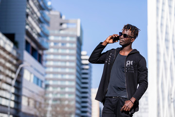 Front view of black man with sunglasses standing against cityscape on the street while using a mobile phone in sunny day.