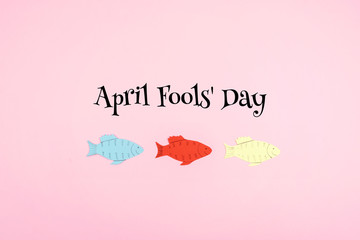 April Fools' Day celebration background with paper fish and text on pink background. All Fools' Day, humor, prank, joke concept