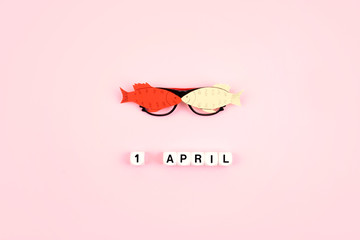 April Fools' Day celebration. Glasses with paper fish and text 1 April on pink background. All Fools' Day, humor, prank, joke concept Wall mural