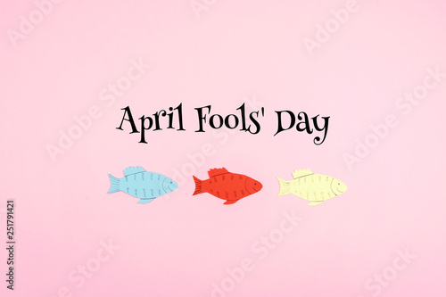 April Fools' Day celebration background with paper fish and text on