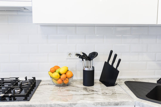 Modern interior decoration of a bright kitchen with sink accesories and fruits