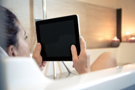 Woman in the water of the bathtub, girl relaxes immersed in a bath relaxing candles atmosphere. Girl working at home with wireless pad in the bathroom. Working anywhere with modern wifi technology