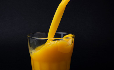 Poster Sap Orange juice pouring into glass, isolated on black background, with copy space
