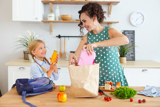 Beautiful brunette mother and her daughter packing healthy lunch and preparing school bag