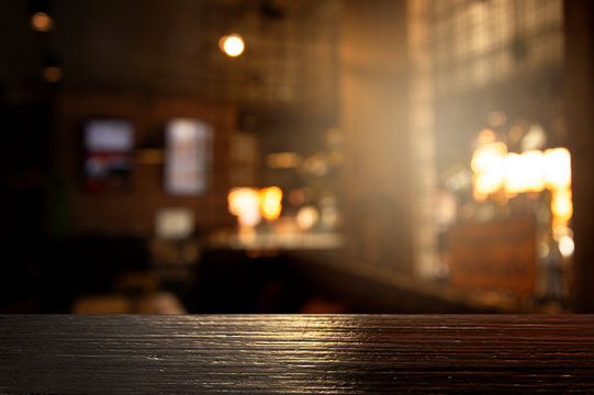 top of black wood with blur light of bar or pub party in the dark night background