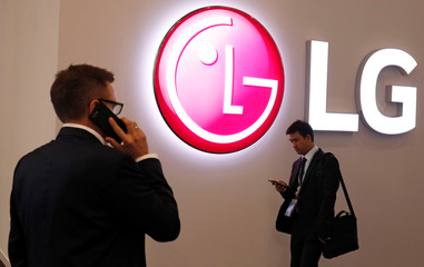Visitors use their mobile phones next to LG booth during the Mobile World Congress in Barcelona