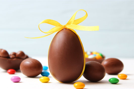 Easter composition with chocolate eggs and chocolate rabbit on wooden background, place for text