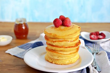 Cornmeal pancakes on a white plate. Served with frozen strawberries and honey or maple syrup.