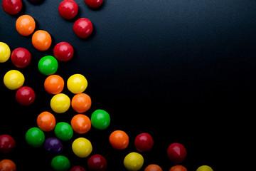 Kolorowe , soczyste cukierki na ciemnym tle.