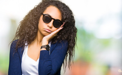 Young beautiful girl with curly hair wearing fashion sunglasses thinking looking tired and bored with depression problems with crossed arms.