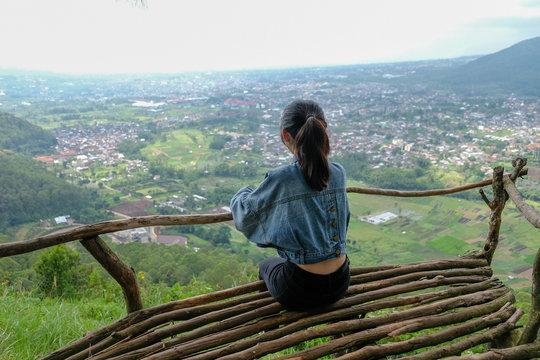 Lonely girl at top hill of Omah Kayu in  Batu Malang, East Java, Indonesia.