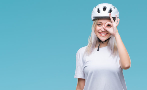 Young blonde woman wearing cyclist security helmet over isolated background doing ok gesture with hand smiling, eye looking through fingers with happy face.