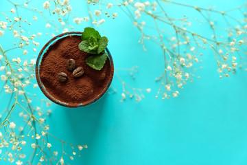 Classic tiramisu in glass on blue background. Italian dessert. Selective focus.