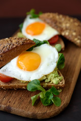 Rye sandwiches (burgers) with avocado, tomato, fried egg and greens on brown wooden background. Selective focus. Healthy eating or vegetarian food concept