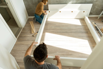 Couple assembling furniture in their new house