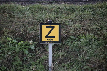 Sign in the side of a ditch to warn that there is an electricity cable sunken in the water