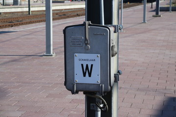 Power switch named W for electricity wires for trains on platform on railroad station Rotterdam Centraal in the Netherlands