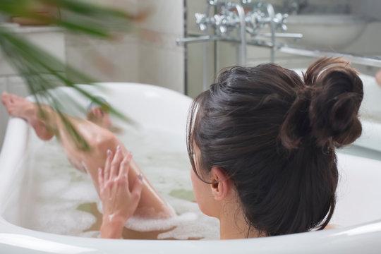 young beautiful brunette woman takes bath