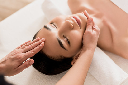 attractive asian woman getting face massage with closed eyes at spa