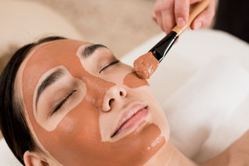 cropped view of beautician applying mask on beautiful woman face