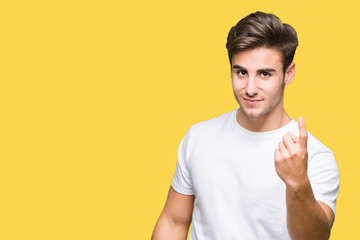 Young handsome man wearing white t-shirt over isolated background Beckoning come here gesture with hand inviting happy and smiling