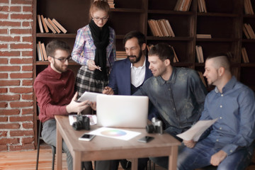 group of designers and photographers use a tablet computer for their work