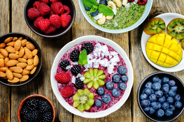Smoothie breakfast bowls with berries, seeds and nuts on a wood background