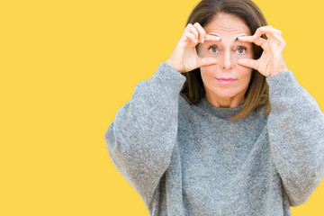 Beautiful middle age woman wearing winter sweater over isolated background Trying to open eyes with fingers, sleepy and tired for morning fatigue Wall mural