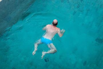 Balding man swimming in clean blue water