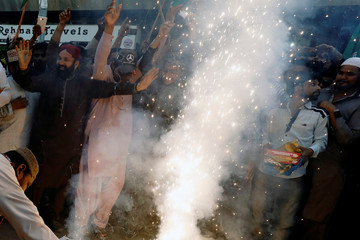 People dance and distribute sweets as they celebrate after Pakistan shot down two Indian military aircrafts, according to Pakistani officials, in Karachi,