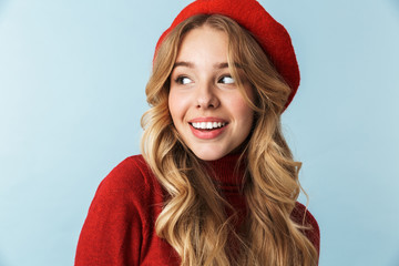 Image of shy blond woman 20s wearing red beret smiling while standing, isolated over blue background in studio Wall mural