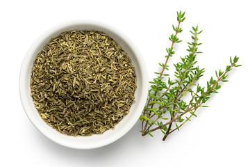 Dried rubbed thyme in a white ceramic bowl next to fresh thyme sprigs isolated on white from above.
